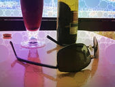 Bottle and a glass of beer with sunglasses in summertime — Stock Photo