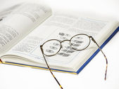 A pair of glasses resting on an open book — Stock Photo
