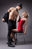 Man show striptease for woman in red — Stock Photo
