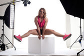 Beauty woman body builder sit on cube in studio — Stock Photo