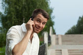 Man call by phone in summer park look at camera — Stock Photo