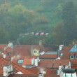 Old Prague roofs at autumn morning with smoke from pipe - Stock Photo