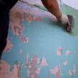 Stock Video: Worker clear wall with trowel from old paint