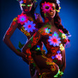 Stock Photo: Nude women with glow uv body art and flowers