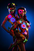 Nude women with glow uv body art and flowers — Stock Photo