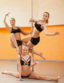 Group of young women posing in pole dance — Stock Photo