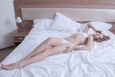 Linda mujer yacía en lencería de cama grande — Foto de Stock