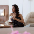 Brunette woman drinking coffee in hotel room — Stock Photo #15862253