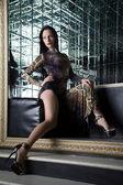 Beautiful young woman sitting on sofa in nightclub — Stock Photo