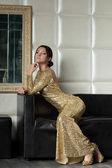 Jeune femme brune en robe or sur canapé — Photo