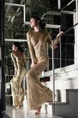 Ung kvinna i guld klänning på trappan — Stockfoto