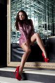 Ziemlich brünette frau posiert im spiegel-nachtclub — Stockfoto