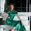 Young womin long green dress sitting on stairs — Stock Photo #18983689