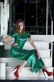 Joven mujer con vestido largo verde sentado en las escaleras — Foto de Stock