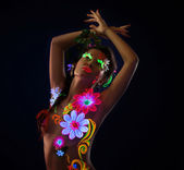 Amazing woman in glowing flowers under uv light — Stock Photo