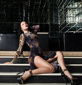 Sexy brunette woman sitting on stairs in nightclub — Stock Photo
