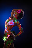Pretty young woman in glowing flowers - uv light — Stock Photo