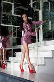 Hübsche frau in mode rosa kleid auf treppe — Stockfoto