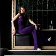 Sexy woman sitting in purple long dress — Stock Photo