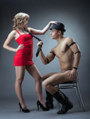 Seductive girl in red playing with stripper — Stock Photo