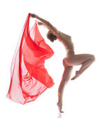 Slender naked woman jumping with cloth in studio — Stockfoto