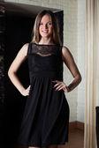 Usměvavá mladá dívka pózuje v černé koktejlové šaty — Stock fotografie