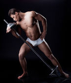 Brawny young man posing kissing barbell — Stock Photo