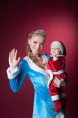 šťastná maminka snow maiden drží dítě santa claus — Stock fotografie