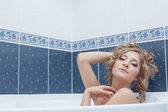 Portrait of languid young woman lying in bath — Stock Photo