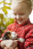 Portrait of smiling little girl looking at cavy — Stock Photo