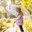 Slyly smiling girl posing under umbrella in park — Stock Photo