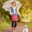 Adorable little girl walking with dog in rain — Stock Photo
