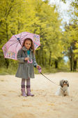 Image of cute little girl walking with dog in park — Stock Photo