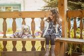 Riccia ragazza seduta in arbor con cucciolo carino — Foto Stock