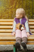 Lovely little girl sitting on bench with her cavy — Stock Photo
