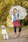 Smiling fashionista posing with dog in park — Stock Photo