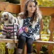 Cute brown-haired girl posing with puppy in gazebo — Stock Photo