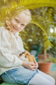 Adorable girl playing with cavy looking at camera — Stock Photo
