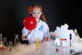 Image of cute little schoolgirl watching reagents — Stock Photo