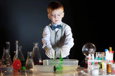 Cute schoolboy watching reaction of reagents — Stock Photo