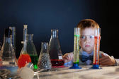 Handsome little boy posing with test-tubes — Stock Photo