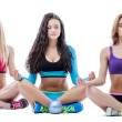 Three relaxed girls meditating in lotus position — Stock Photo