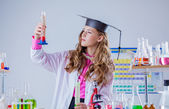 Image of high school girl looking at test tube — Stock Photo