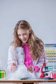 Smiling student looking at reaction of reagents — Stock Photo