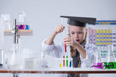 Surprised girl looking at test tubes with reagents — Stock Photo