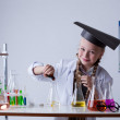 Stock Photo: Smiling chemist mixes reagents in flask, close-up