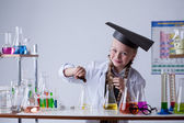 Smiling chemist mixes reagents in flask, close-up — Stock Photo
