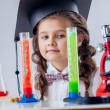 Stock Photo: Curious little girl posing with microscope in lab
