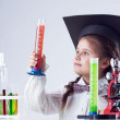 Stock Photo: Smart little experimenter looking at test tube