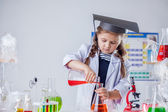Image of cute chemist pours reagent into flask — Stock Photo